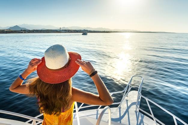 黄色のドレスと青い海の水の景色を楽しみながら白いヨットのデッキに立っている麦わら帽子を身に着けている長い髪の若い女性。