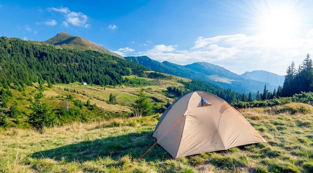 Туристическая палатка в горах в солнечный летний день