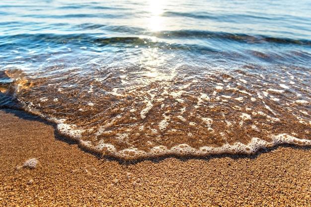 Крупным планом небольших морских волн с прозрачной голубой водой над желтым песчаным пляжем в солнечный летний берег.