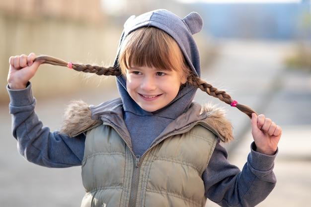 Портрет счастливой девочки ребенка с косичками в теплой одежде осенью на открытом воздухе