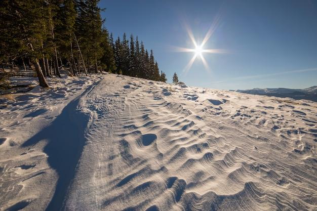 雪景色の丘と遠くの白い山のある冬景色のパノラマ
