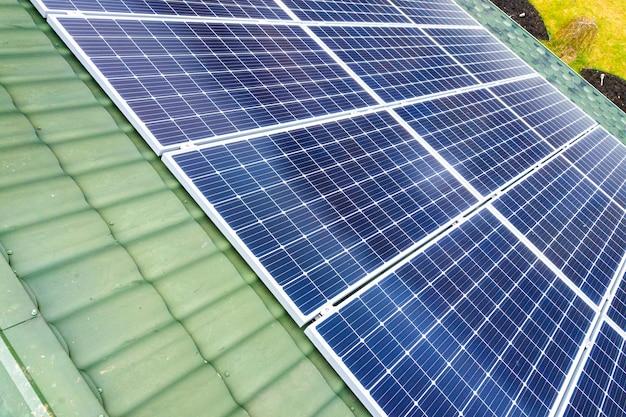 Воздушный взгляд сверху нового современного жилого коттеджа дома с голубой сияющей солнечной системой фотоэлектрических панелей на крыше. концепция производства возобновляемой экологической зеленой энергии.