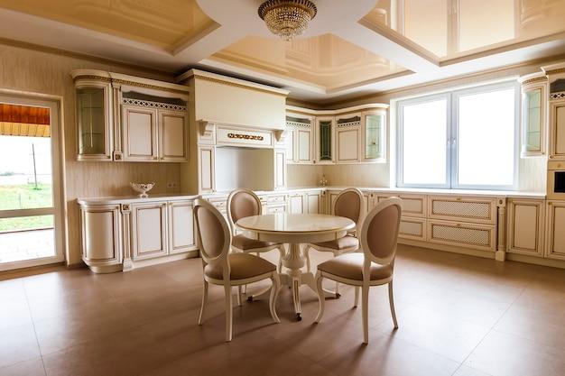 豪華なモダンなキッチンインテリア。ベージュのキャビネットが付いている贅沢な家の台所。テーブルと椅子