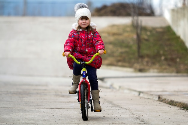 Красивые улыбающиеся маленькая девочка, езда на велосипеде в парке