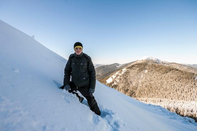 氷河の上を上り坂を歩く男性登山家。登山家は晴れた冬の日に雪に覆われた山の頂上に到達します。