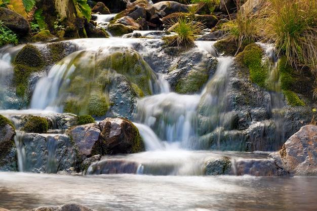 美しい滑らかな水と公園内の小さな滝。シルキーな泡立つ水と山の森の小さな滝。