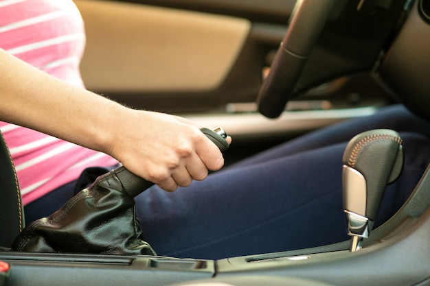 Крупным планом женского водителя рукой, держащей ручной тормоз в автомобиле