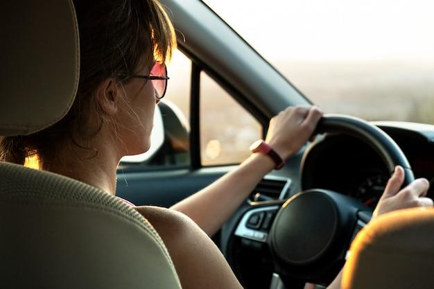 Женщина водитель держит руль за рулем автомобиля на закате