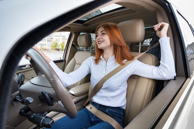 車を運転するシートベルトで固定された若い女性ドライバー