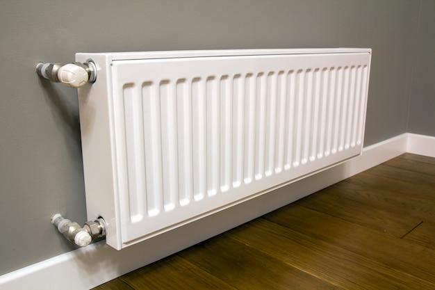 Белый металлический радиатор отопления установлен на серую стену