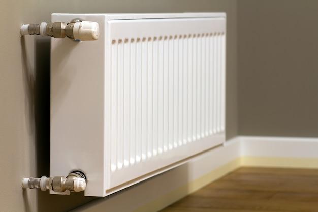 Белый металлический радиатор отопления на серой стене