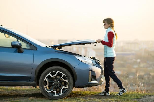 壊れた車のボンネットを開く若い女性