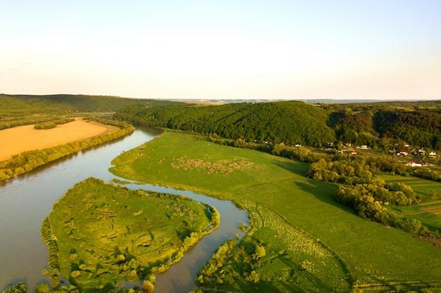 春の緑の牧草地を流れる明るい川の空撮。