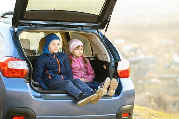 Два счастливых детей мальчик и девочка, сидели в багажнике автомобиля.