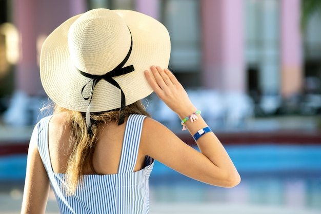 軽い夏のドレスと夏の晴れた日にホテルのプールの近くに外に座っている黄色の麦わら帽子を着た若い女性。