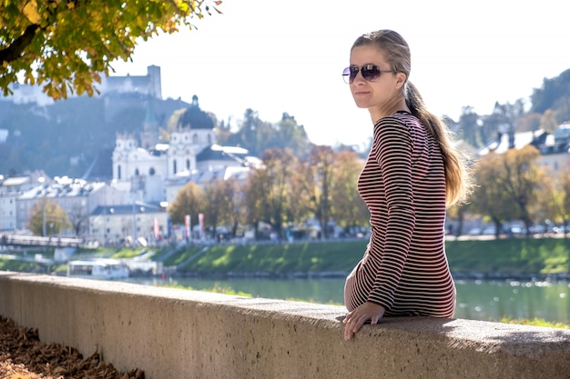 Молодая женщина в повседневные платья и солнцезащитные очки, отдыхая на открытом воздухе в теплый осенний день.
