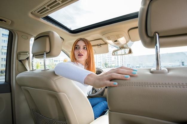 Широкоугольный вид молодой рыжий женщина водитель за рулем автомобиля, оглядываясь назад.