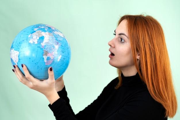 世界の地理的な地球を手に持った悲しい心配している若い女性の肖像画。旅行先と惑星保護のコンセプト。