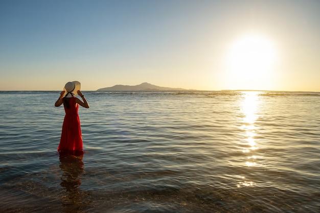初夏の朝に昇る太陽の景色を楽しみながらビーチで海の水に長い赤いドレスと立っている麦わら帽子を着た若い女性。