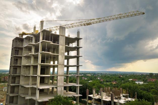Аэрофотоснимок подъемного крана башни и бетонного каркаса жилого дома высокой квартиры под строительство в городе. концепция городского развития и роста недвижимости.