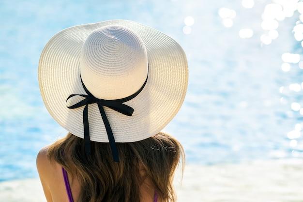 晴れた日に青い水とスイミングプールのそばの夏にリラックスできる麦わら帽子をかぶって長い髪の若い女性の背面図。