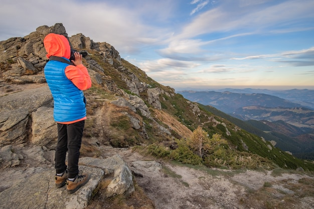 若い子の少年ハイカーが素晴らしい山の風景の景色を楽しみながら山で写真を撮る。
