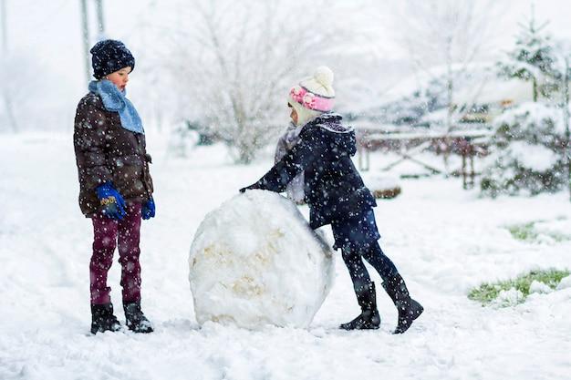 雪の降る冬の屋外で子供男の子と女の子が大きな雪だるまを作っています。