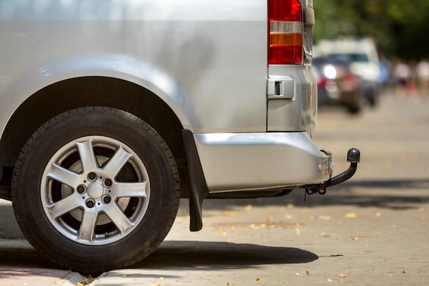 Детальный вид сбоку крупным планом серебряного пассажирского микроавтобуса среднего размера класса люкс с буксирной тягой, припаркованной на тротуаре в солнечный летний город