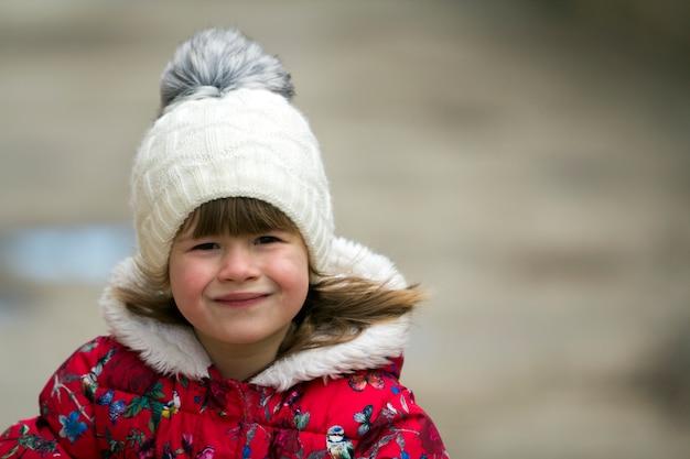白い背景の上の暖かい服でかわいい女の子。