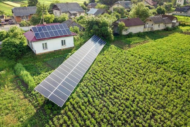 青い太陽電池パネルが付いている家の空撮