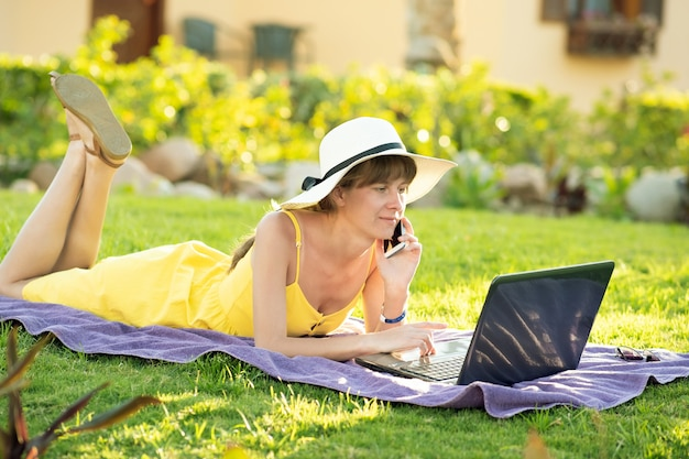 モバイル携帯電話で会話しているコンピューターのラップトップで勉強している緑の芝生で休んでいる黄色の夏のドレスの女子生徒。