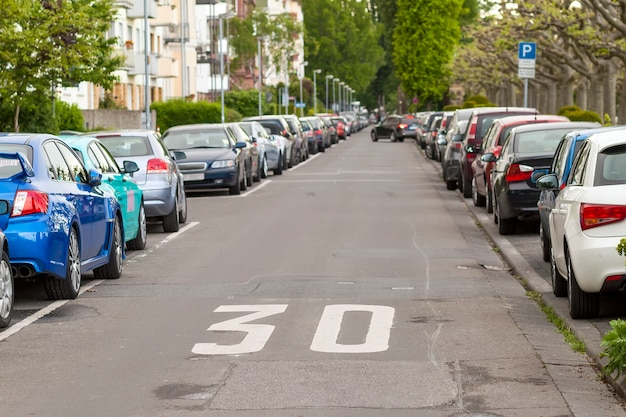 Ряды автомобилей, припаркованных на обочине дороги в микрорайоне