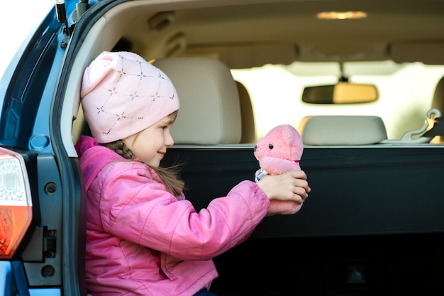 車のトランクにピンクのおもちゃのテディベアで遊んでかなり幸せな子供の女の子。