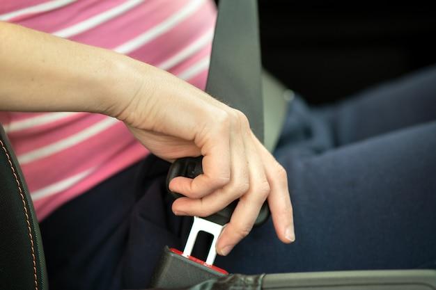 安全のために車の中に座って道路を運転する前にシートベルトを締めている女性の手のクローズアップ。