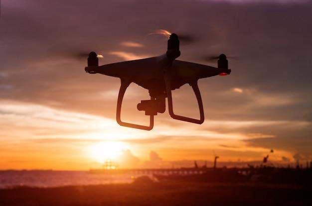 Силуэт беспилотный летающий во время заката.