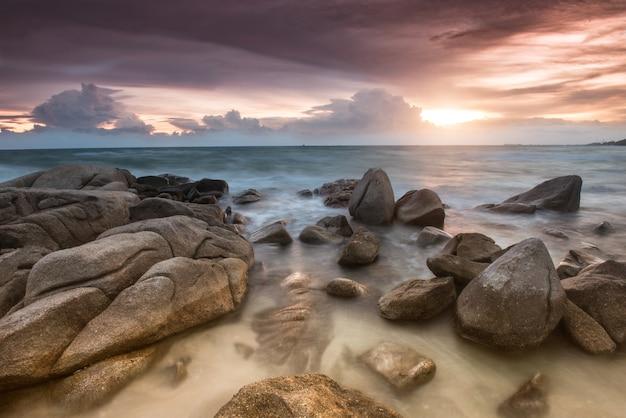 Скала и море цвета заката.