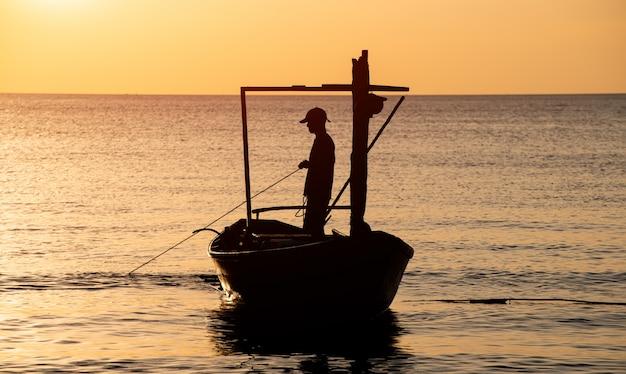 Силуэт времени захода солнца шлюпки и рыболова.
