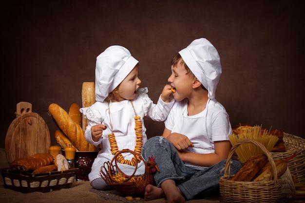 Два мальчика и девочка с удовольствием кормит друг друга печеньем, позируя, играя в шеф-повара