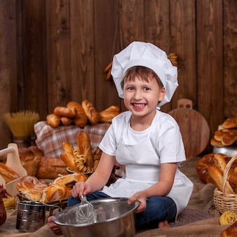 ベビークックは服を着て泡立て器小麦粉ベーカーたくさんのパンを防ぎます