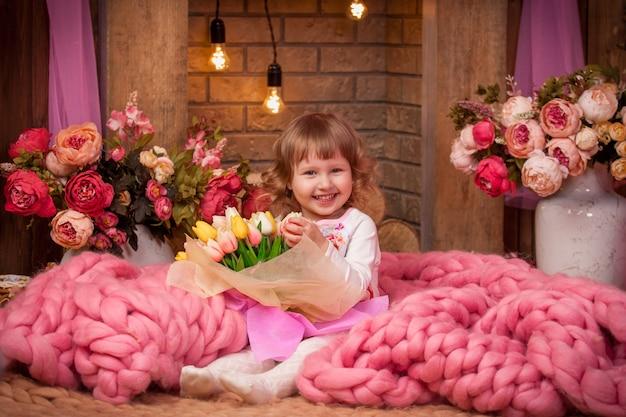 彼女の手に花を持つメリノウールの毛布で座っている美しい少女