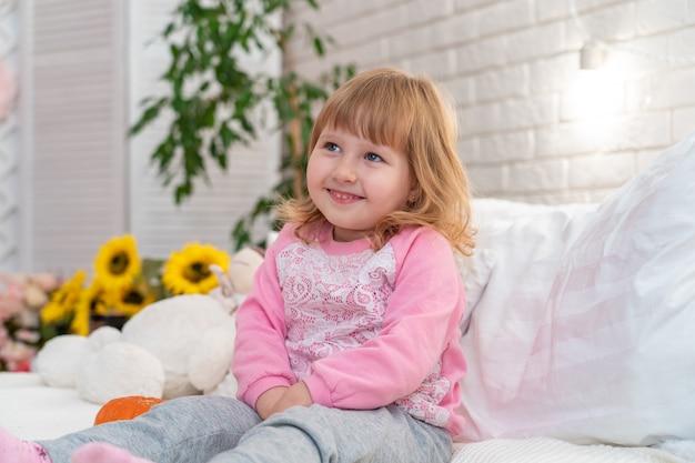 Маленькая девочка сидит на кровати у себя дома
