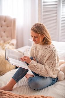 Женщина читает книгу на кровати