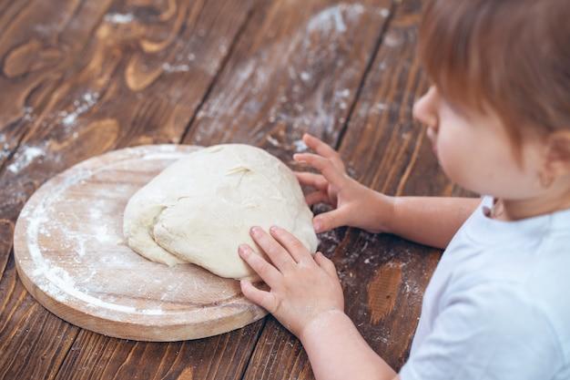 Тесто в руках у ребенка, деревянный стол. взято с плеча.