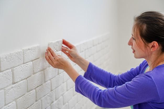 Девушка крепит на стену декоративный кирпич