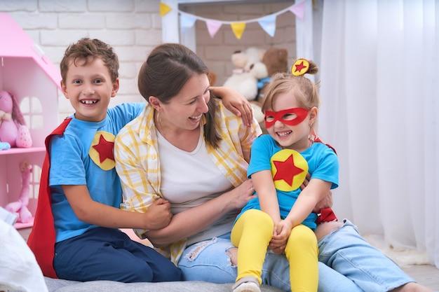 幸せな家族。若い女性がスーパーヒーローで子供たちと遊ぶ。
