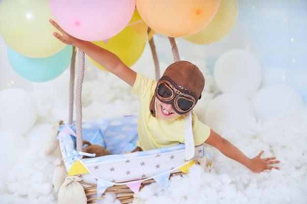 小さな男の子が雲の中の気球のかごの中に座って、旅行や飛行のふりをして、創造性や想像力の概念を求める飛行士の帽子をかぶっています。