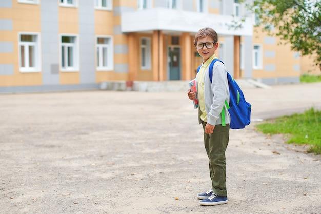Обратно в школу. мальчик из начальной школы у школьного двора.