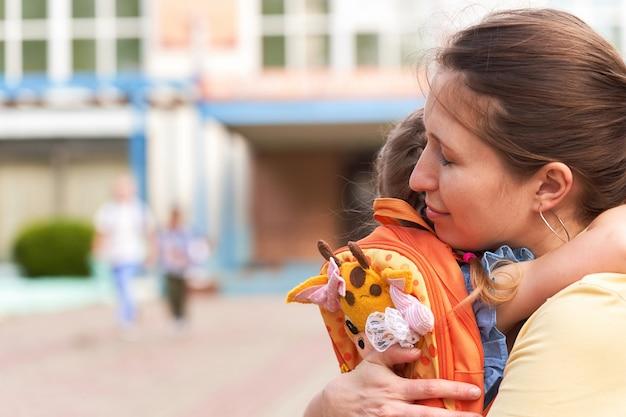 女性は学校の近くで娘を抱擁します。女の子は母親から離れたくない。