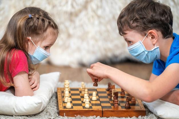 Дети играют в шахматы в медицинских масках на лице, лежат на полу. останься дома