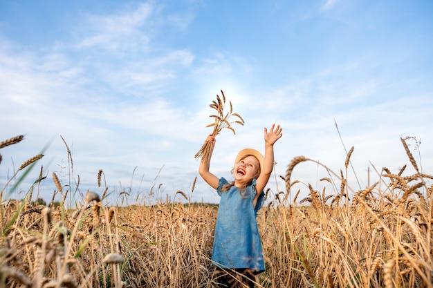 麦畑で幸せな子供は彼の手を上に引っ張る